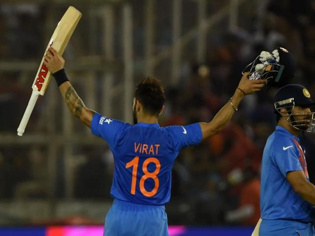 India's captain Mahendra Singh Dhoni(R) walks with teammate Virat Kohli as they celebrate after victory.