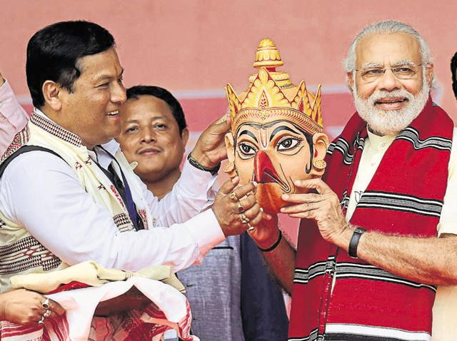 BJP's CM candidate Sarbananda Sonowal gifts PM Modi a traditional Assamese mask in an election rally. Sonowal (eft) blames the increase in number of communal incidents on the Congress and the AIUDF.(Ujjal Deb / HT Photo)