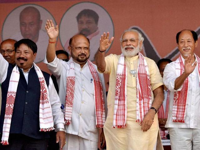Prime Minister Narendra Modi with Praful Kumar Mahanta and other AGP-BJP leaders waves during an election rally at Bokakhat in Golaghat district of Assam.