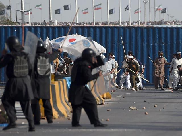 Pakistani police fire tear gas to stop protesters from marching towards the parliament building in Islamabad, Sunday, March 27, 2016.