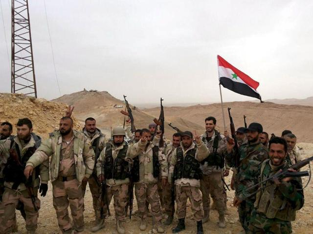 Troops loyal to Syrian President Bashar al-Assad celebrate in Palmyra. State media has reported that the army is in full control of the desert city, which has been under the control of Islamic State since last year.