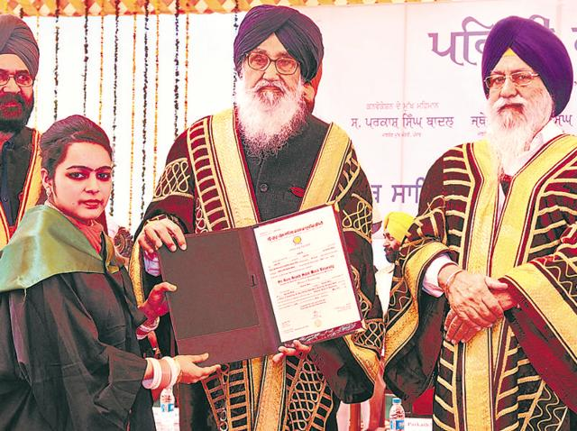 A student collecting her degree from Punjab chief minister Parkash Singh Badal during the first annual convocation of Sri Guru Granth Sahib World University in Fatehgarh Sahib on Saturday, as Shiromani Gurdwara Parbandhak Committee president Avtar Singh Makkar (right) looks on.