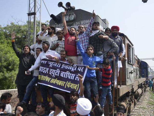 Jewellers and goldsmiths sitting on a rail track to block rail traffic at the Shivla railway crossing in Amritsar on Monday.