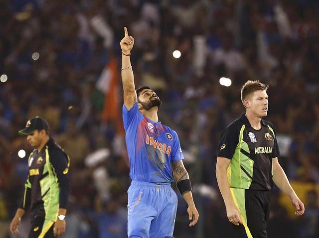 Virat Kohli celebrates as Australia's James Faulkner (R) and Usman Khawaja walk after India won the World T20 match.