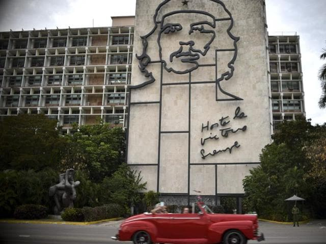 A vintage car drives past a sign at Revolution square in Havana, Cuba on March 19, 2016.