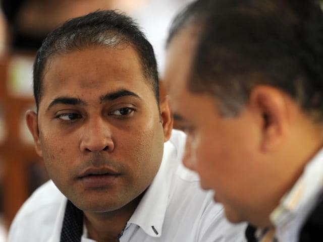 Sayed Mohammed Said speaks with his lawyer in the courtroom before the start of proceedings he attends his sentencing on drugs related charges in Denpasar on Indonesia's resort island of Bali.