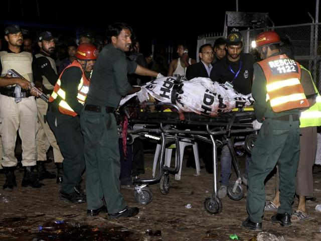 Pakistani rescue workers remove a dead body from the site of bomb explosion in a park in Lahore, Pakistan.
