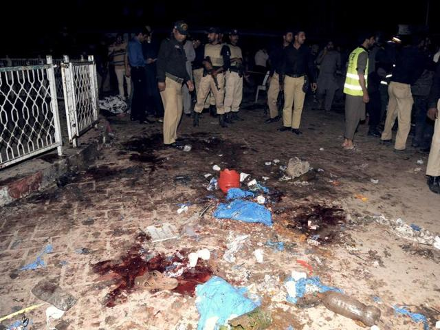 Pakistani emergency workers and police officers gather at a bomb blast site in Lahore.