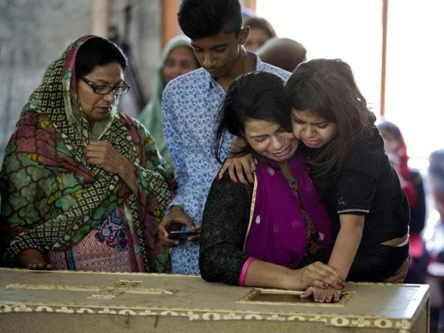 A Pakistani Christian looks at her son's coffin as she holds her daughter.