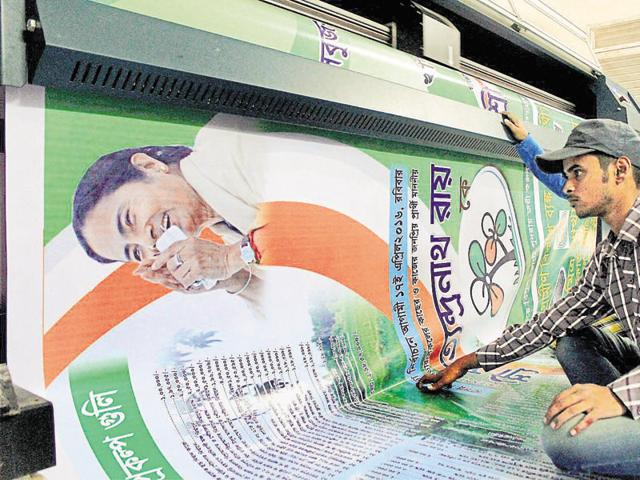 TMC workers carry giant hoardings of West Bengal CM Mamata Banerjee for the upcoming assembly elections in Kolkata on March 18.