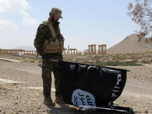 A member of the Syrian pro-government forces carries an Islamic State (IS) group flag as he stands on a street in the ancient city of Palmyra on Sunday  after troops recaptured the city from IS jihadists.