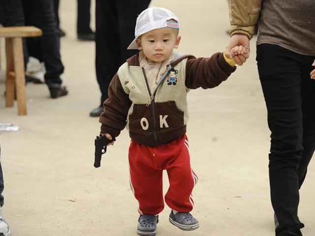 A child walks with his toy gun walks with his mother. A Chinese expert has warned that 100 million children from migrant labourers have been left behind in the country.