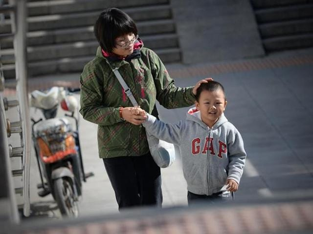 A woman takes a child's hand as they walk through an underpass in Beijing.