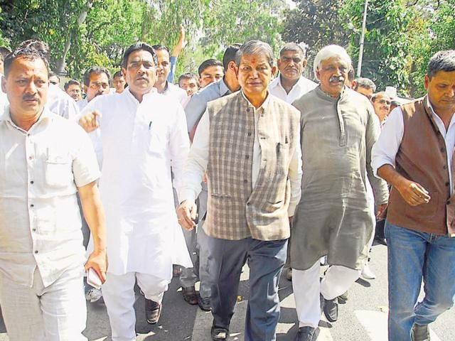 Former CM Harish Rawat, with his supporters, leaves the Governor's house on Monday.