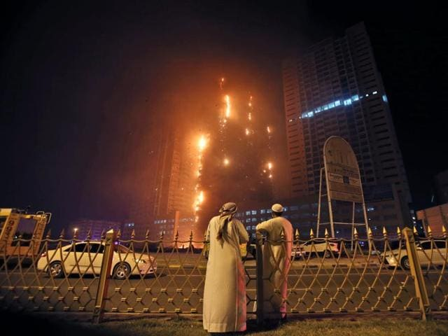 Two Emirati officials watch a high-rise building as a fire spreads up the side of the building in Ajman.