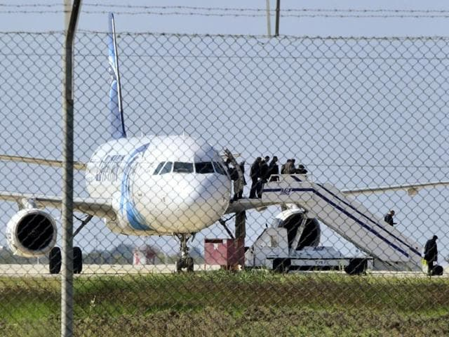 Police stand guard at Larnaca Airport near a hijacked Egyptair Airbus A320 , March 29, 2016.