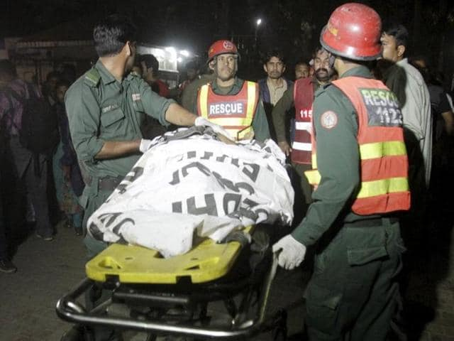 Rescue workers move a body from the site of a blast outside a public park in Lahore on March 27, 2016.