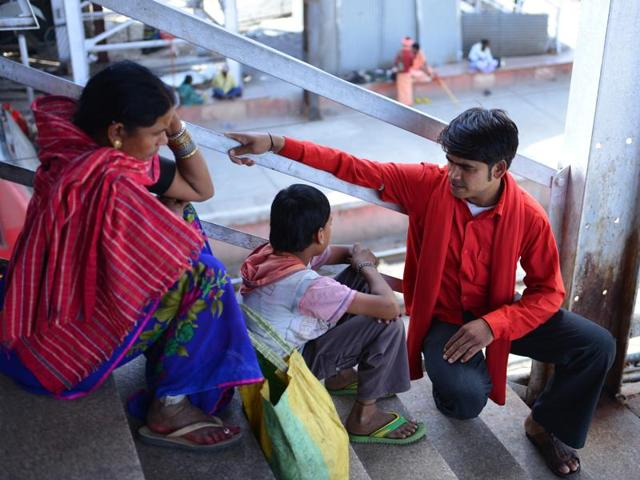 A coolie trying to gather information from a child roaming around at railway station in Bhopal.