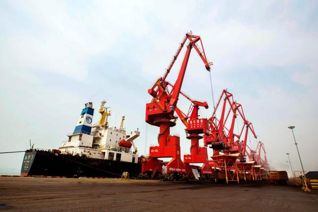 Imported coal being unloaded from a cargo ship at a port in Lianyungang, east China's Jiangsu province. Huge industrial overcapacity will drag on China's growth this year, the Asian Development Bank (ADB) said in its report.