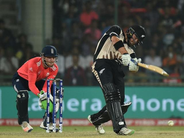 New Zealand's Corey Anderson(R) plays a shot as England's wicketkeeper Jos Buttler looks on during the World T20 cricket tournament first semi-final match between England and New Zealand at The Feroz Shah Kotla Cricket Ground in New Delhi on March 30, 2016.
