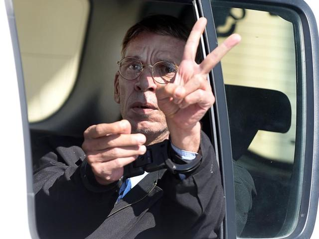 Seif al-Din Mohamed Mostafa, an Egyptian man who hijacked an EgyptAir passenger plane the previous day and forced it to divert to Cyprus demanding to see his ex-wife, flashes the 'V' for victory sign as he leaves the court in Larnaca.