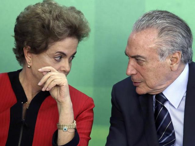 File photo of Brazil's President Dilma Rousseff talks with her Vice President Michel Temer. The Brazilian Democratic Movement Party, (PMDB), of which Temer is the leader, said on Tuesday, March 29, 2016, that its members are leaving Rousseff's governing coalition.