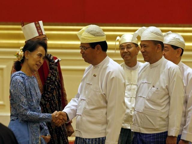 Newly sworn-in Myanmar foreign minister Aung San Suu Kyi (centre) and Myanmar vice president Henery Van Thio (right) leave after the handover ceremony at the presidential palace in Naypyidaw on Wednesday.