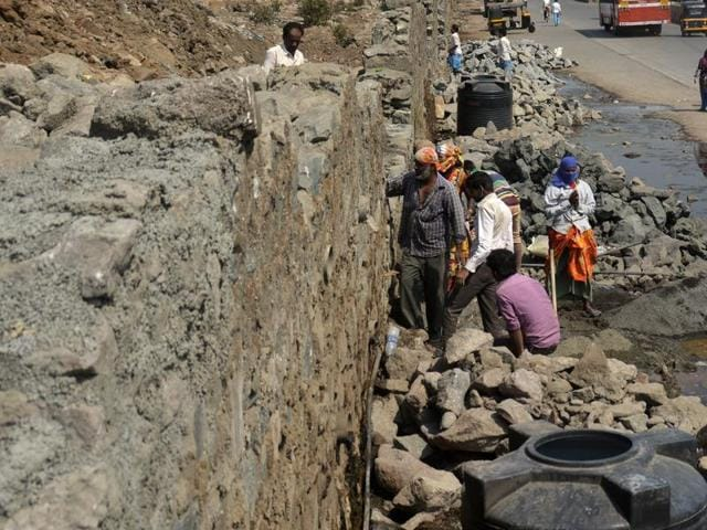 The boundary wall of Deonar dumping ground being repaired on Wednesday.
