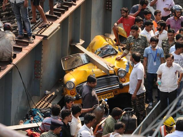 People gather around a mangled vehicle after an under-construction flyover  collapsed in Kolkata on Thursday.