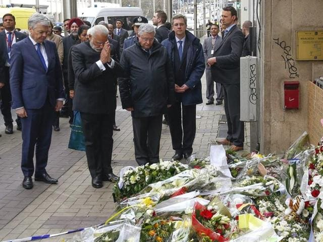 Belgium's foreign minister, Didier Reynders (L), and Indian Prime Minister Narendra Modi (C) pay tributes to the victims of Brussels attack.