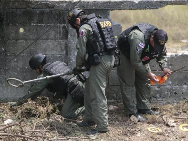 Military personnel inspect the site of a bomb attack at Yaring district in the troubled southern province of Pattani, Thailand.