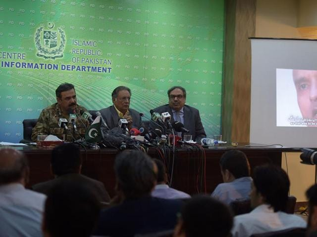 Pakistani Lt Gen Asim Bajwa (L) speaks with the media as he gives details of an arrested man, Kulbhushan Yadav (R on screen), who Islamabad says is an Indian spy.