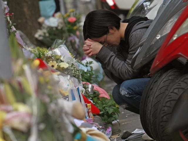 In this Tuesday, March 29, 2016 file photo, a woman prays in front of a makeshift memorial offered with flowers and stuffed animals for a girl who was killed Monday by a knife-wielding assailant outside a subway station in Taipei, Taiwan.