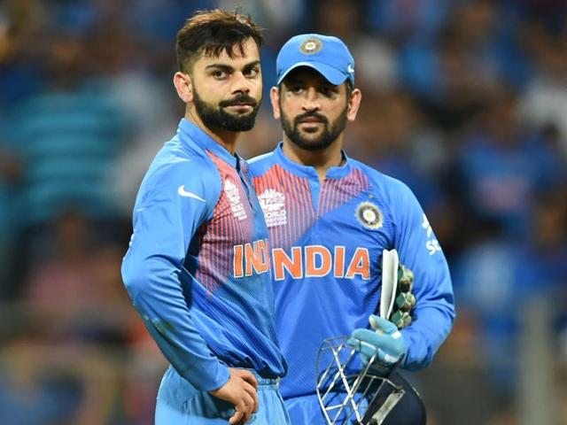 India's Virat Kohli(L) and captain Mahendra Singh Dhoni look on after defeat in the World T20 cricket tournament second semi-final match between India and West Indies at The Wankhede Stadium in Mumbai on March 31, 2016.