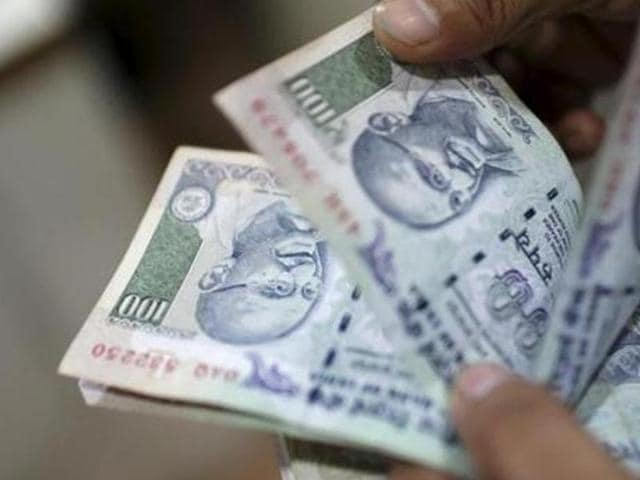 An employee counts currency notes in New Delhi in this July 5, 2013 file photo. Interest rates on small saving schemes including PPF have been slashed from April 1, 2016.
