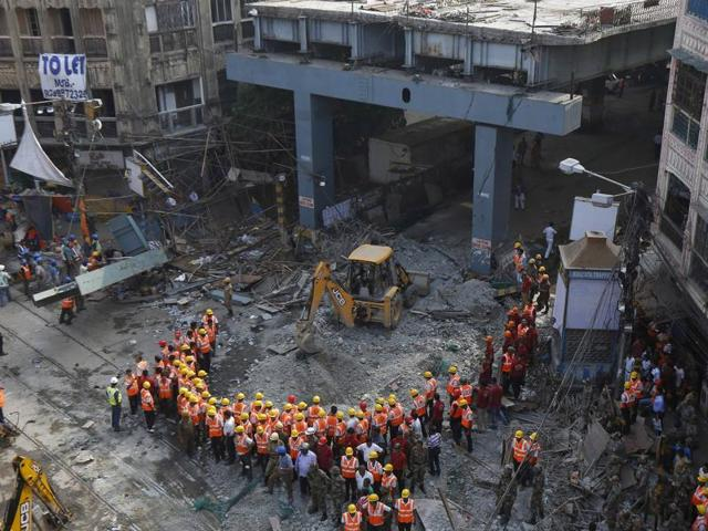 Members of the National Disaster Response Force remove the remains of a person from the rubble of an under-construction flyover that collapsed in Kolkata,