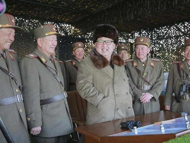 North Korean leader Kim Jong Un smiles with military officers as he observes a military drill at an unknown location, in this undated photo released by North Korea's Korean Central News Agency (KCNA) on March 25, 2016.