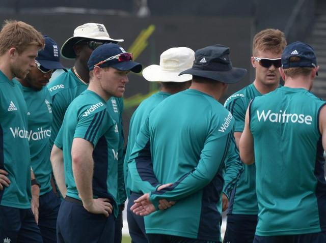 England's captain Eoin Morgan (C) stands with teammates during a training session.