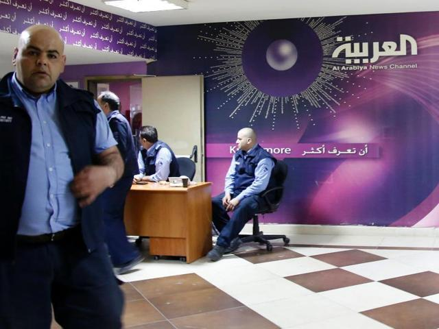 Security staff members stand guard at the entrance of the offices of  Al-Arabiya news channel on Friday in the Lebanese capital Beirut.