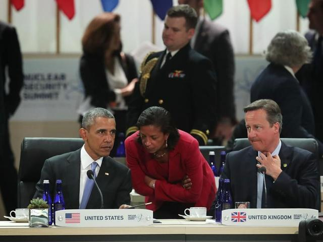US President Barack Obama talks to his National Security Adviser Susan Rice as UK's Prime Minister David Cameron looks on at the Nuclear Security Summit in Washington.