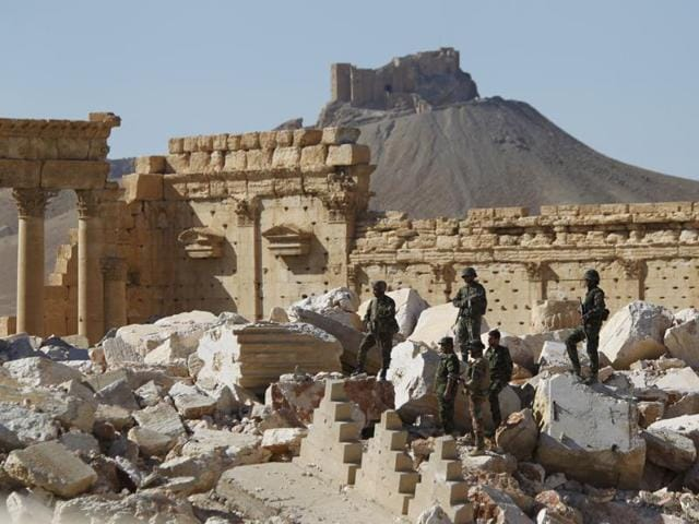 Syrian army soldiers stands on the ruins of the Temple of Bel in the historic city of Palmyra.
