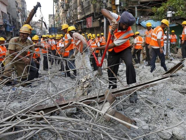 A rescue worker cuts iron rods amid the debris at the site of an under-construction flyover that collapsed on Thursday in Kolkata.