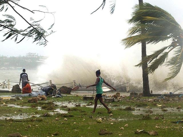 Local residents walk past debris as a wave breaks nearby in Port Vila, the capital city of the Pacific island nation of Vanuatu when a cyclone struck the island last year.