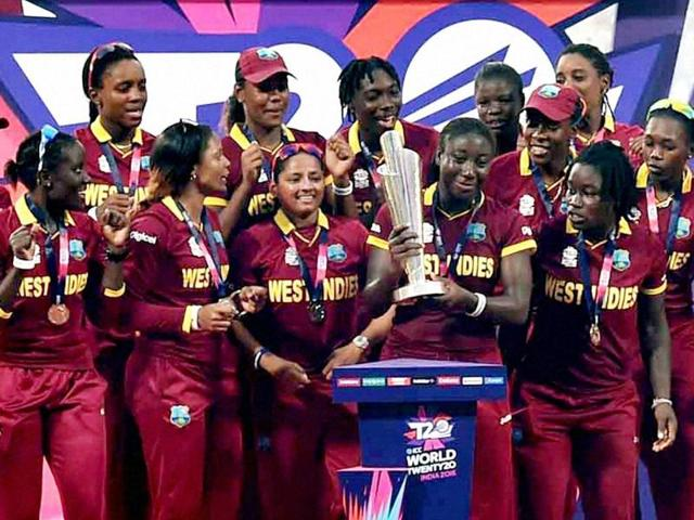 ICC Women's World T20 2016 champion West Indies cricketers celebrate with the champion's trophy.