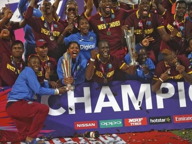 West Indies captain Darren Sammy holds aloft the nation's men's and women's World T20 titles.