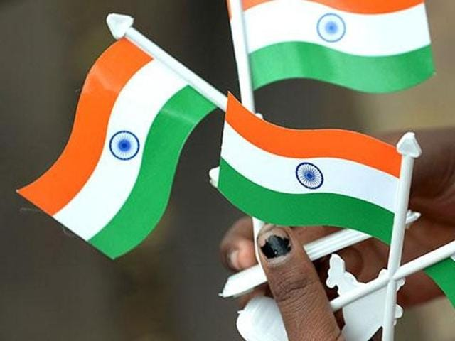 A girl sells miniature tricolour flags waits for customers at the corner of a busy crossroad in Mumbai.  A debate on what constitutes nationalism is currently on in the country.