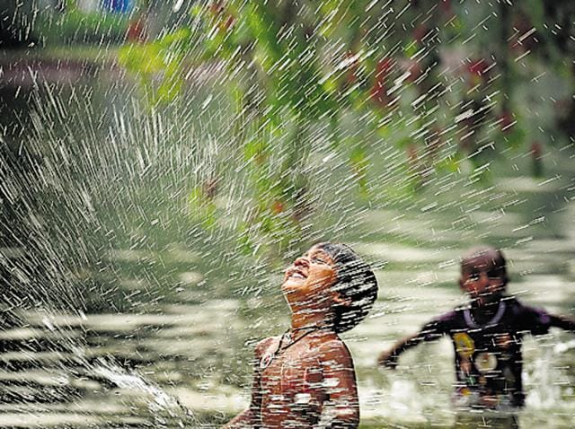 Children beat the heat with a dip in the pond at India Gate on Sunday. At least three places in the city breached the 40-degree mark.