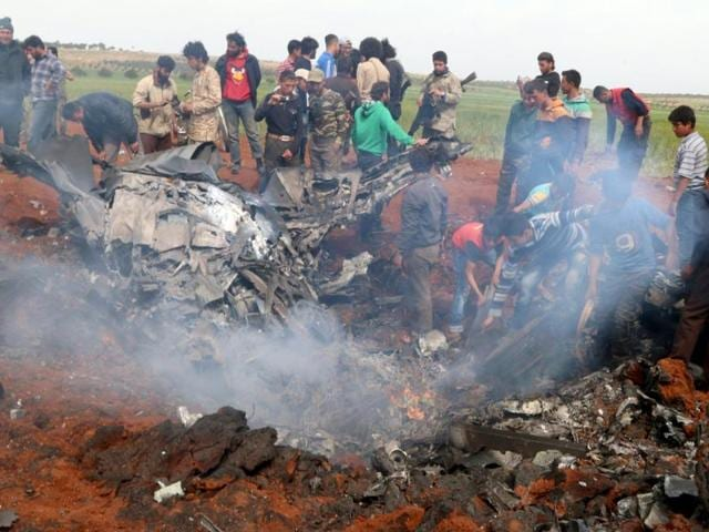 Rebel fighters and civilians gather around the wreckage of a Syrian warplane that was shot down in the Talat al-Iss area, south of Aleppo.