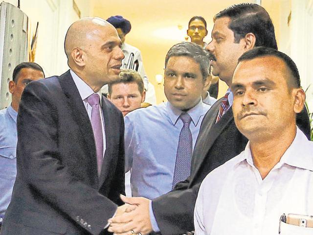 Britain's business secretary Sajid Javid (L) shakes hands with Tata Steel Group CFO Koushik Chatterjee as he leaves the Bombay House, the group's head office in Mumbai.