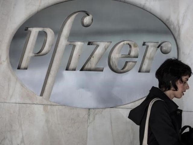The Pfizer logo appears on a screen above its trading post on the floor of the New York Stock Exchange, Wednesday, April 6, 2016. The biggest US-based drugmaker has decided not to go ahead with its merger with Irish firm Allergan citing new US tax rules.